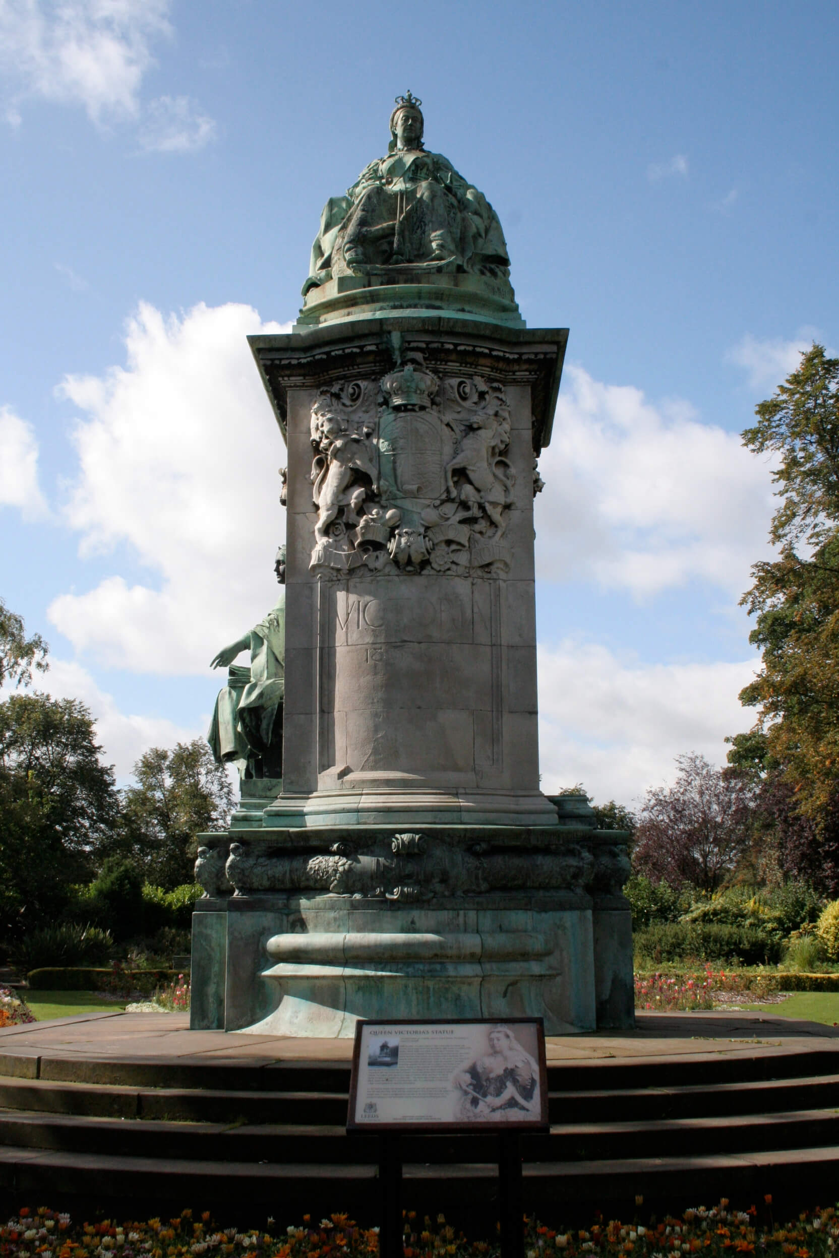 Photo of the memorial to Queen Victoria which is a short plinth with the monarch seated at the top