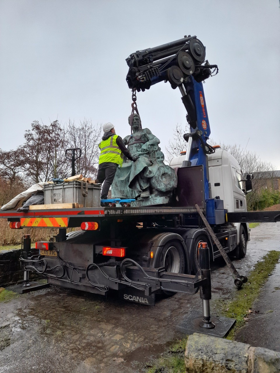 The statue of Queen Victoria is secured to the back of a lorry for transport